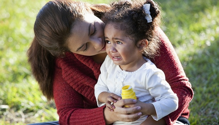 Hispanic mother comforting crying daughter